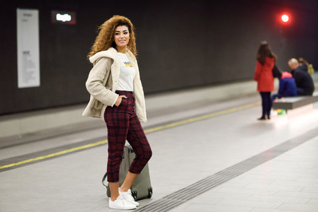 Young arabic woman waiting her train in a subway station