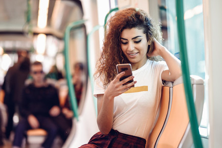 Arabic woman inside subway train looking at her smartphone
