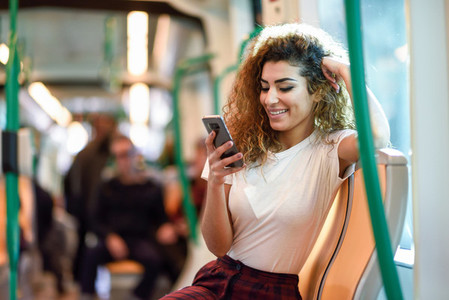 Arab woman inside subway train looking at her smartphone
