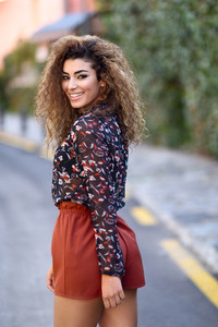 Happy young arabic woman with black curly hairstyle