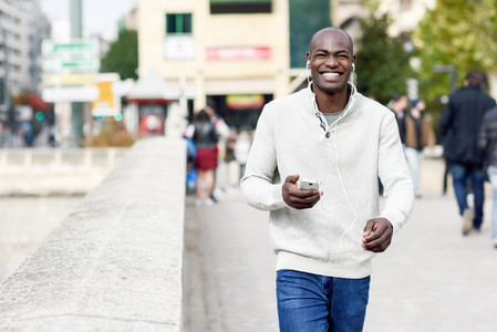 Black young man with a smartphone in his hand in urban backgroun