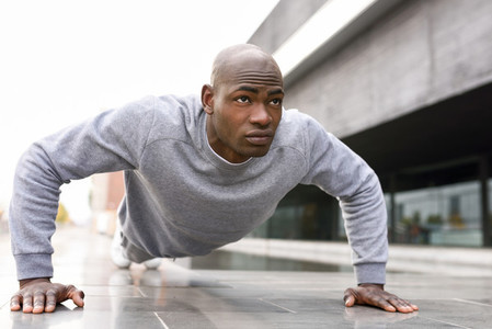 Fitness black man exercising push ups in urban background