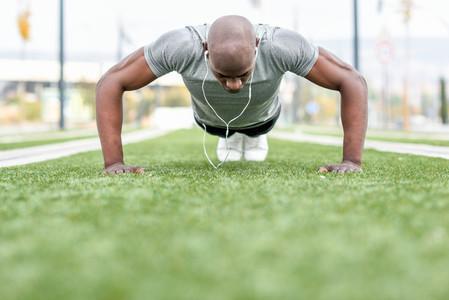 Fitness black man exercising push ups in urban background