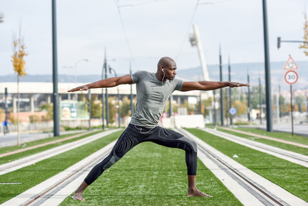Black man practicing yoga in urban background