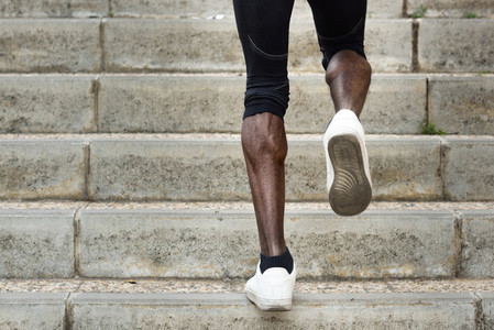 Athletic legs of black man running on staircase steps