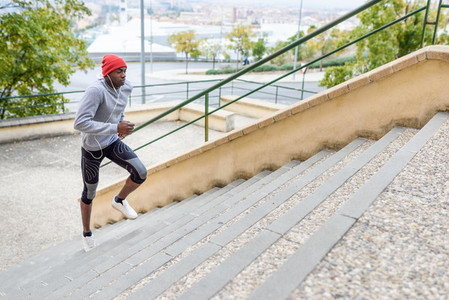Black man running upstairs outdoors in urban background