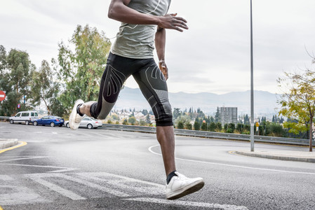 Black man running outdoors in urban road