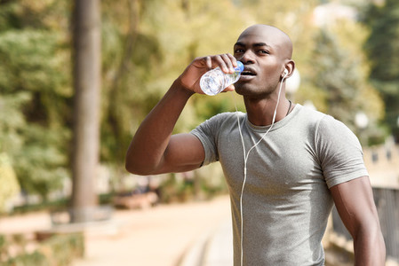 Young black man drinking water before running in urban backgroun