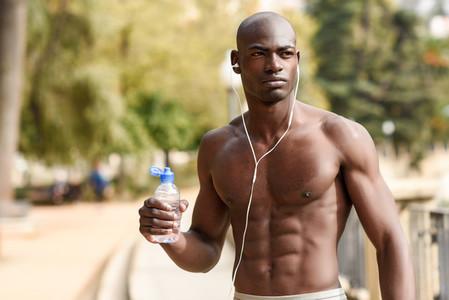 Black man drinking water after running in urban background