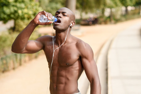 Black man drinking water after running in urban background