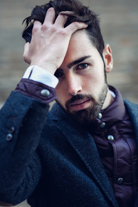 Young bearded man wearing british elegant suit touching his hair