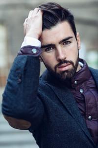 Young bearded man wearing british elegant suit touching his hair