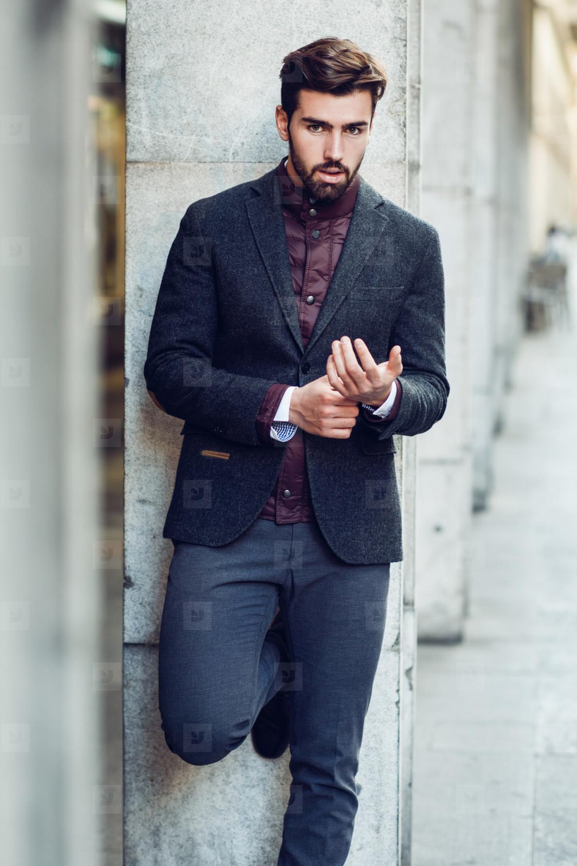 Young bearded man in urban background wearing british elegant su