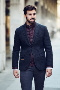 Young bearded man smiling in urban background wearing british el