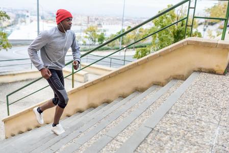Black man running upstairs outdoors in urban background