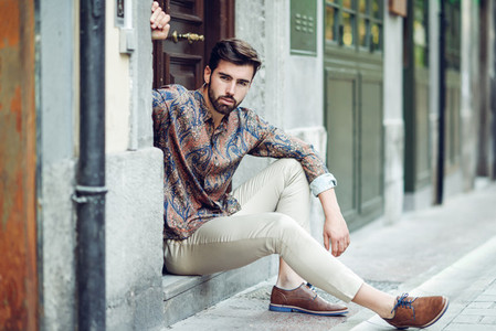 Young bearded man model of fashion sitting in an urban step we