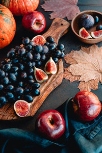 Autumn food still life with season fruits and vegetables like Bangalore blue grape pumpkins  red apples and figs on a table