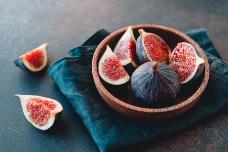 Macro photo of ripe quartes figs in a wooden small bowl on a table