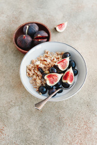 Close up view of a breakfast bowl with granola blue grape and fig slices Healthy vegan eating