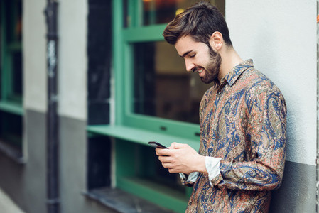 Young man wearing casual clothes looking at his smartphone in th