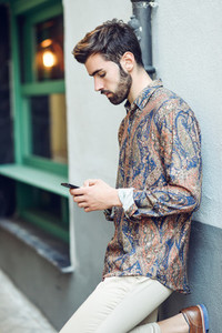 Young man wearing casual clothes looking at his smartphone in the street