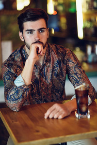 Thoughtful bearded man wearing casual clothes sitting in a modern pub