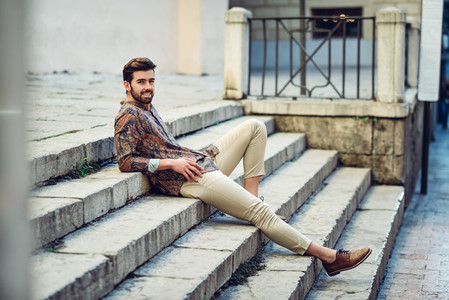 Young bearded man model of fashion wearing shirt in urban back