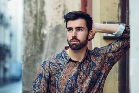 Young bearded man  model of fashion  wearing shirt in urban back