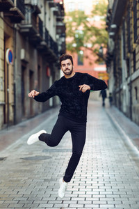 Young bearded man jumping in urban background with open arms wearing casual clothes