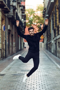 Young bearded man jumping in urban background with open arms wea