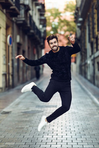 Young bearded man jumping in urban street wearing casual clothes