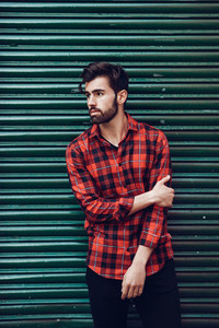 Young bearded man  model of fashion  wearing a plaid shirt with a green blind behind him