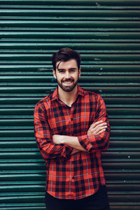 Young bearded smiling man wearing a plaid shirt with a green bli