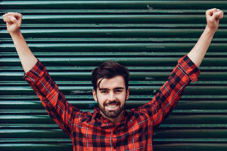 Young smiling man  open arms  wearing a plaid shirt with a green