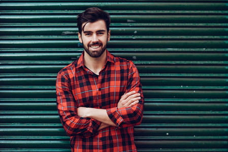 Young smiling man  model of fashion  wearing a plaid shirt with