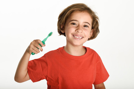 Happy little girl brushing her teeth with a toothbrush