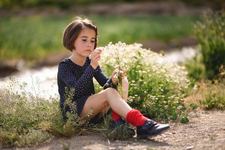 Little girl sitting in nature field wearing beautiful dress
