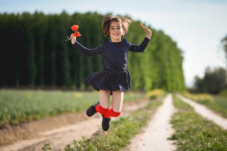 Little girl walking in nature field wearing beautiful dress