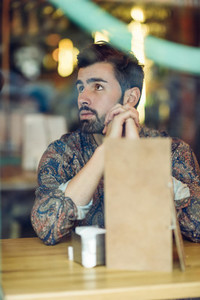 Thoughtful bearded man wearing casual clothes sitting in a moder