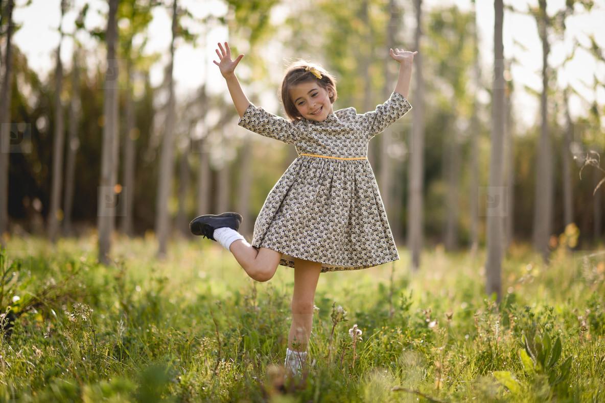 Little girl in nature field wearing beautiful dress