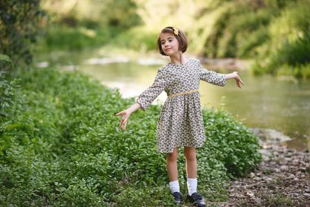 Little girl in nature stream wearing beautiful dress