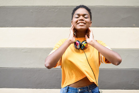 Happy African woman smiling on urban wall with eyes closed wearing casual clothes and headphones