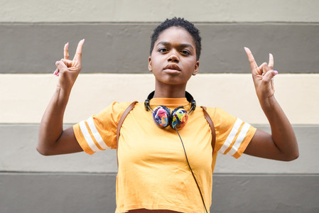 Young black woman making the gesture of the horns with her hands outdoors