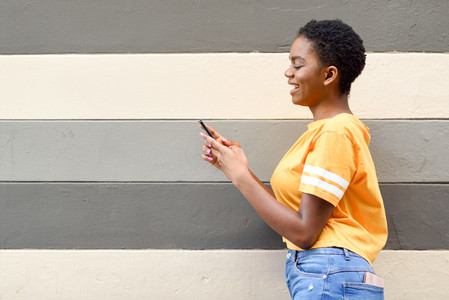 Black girl smiling and using her smart phone outdoors