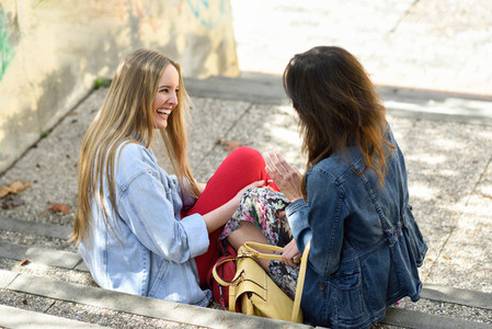 Two young women talking and laughing on urban steps