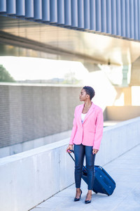 Black woman walking with travel bag wearing pink jacket
