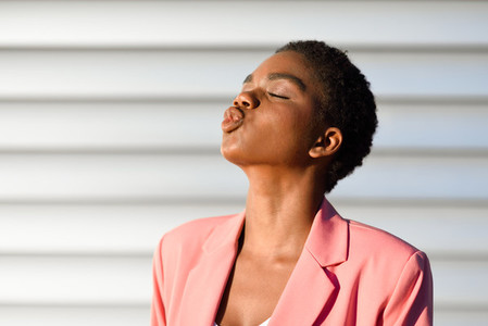 Black woman  with very short hair blowing a kiss