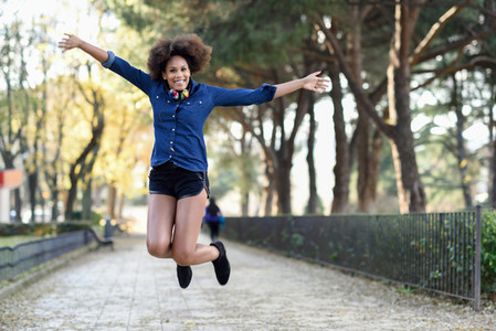 Young black woman with afro hairstyle jumping in urban backgroun