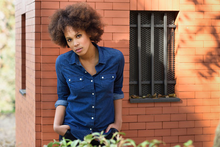 Young black woman with afro hairstyle standing in urban backgrou
