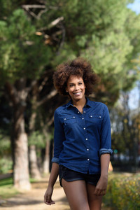 Young black woman with afro hairstyle walking in urban park